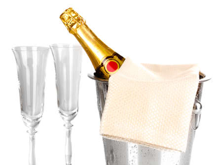 Champagne bottle in bucket with ice and glasses isolated on white photo