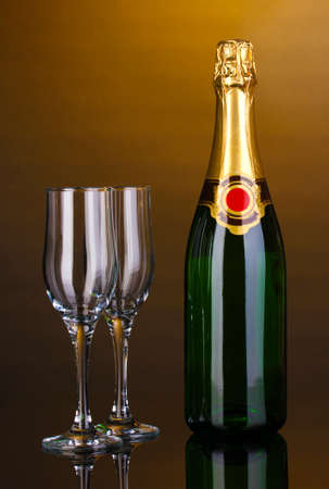 gold capped: Bottle of champagne and goblets on brown background
