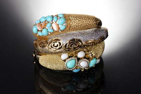 Beautiful golden bracelets on grey background photo