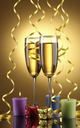 glasses of champagne, candles, gifts and streamer on yellow background photo