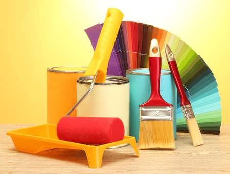tin cans: blikjes met verf, rol, borstels en heldere palette van kleuren op houten tafel op gele achtergrond