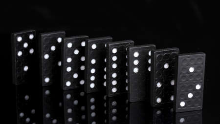 cause and effect: Dominoes isolated on black Stock Photo