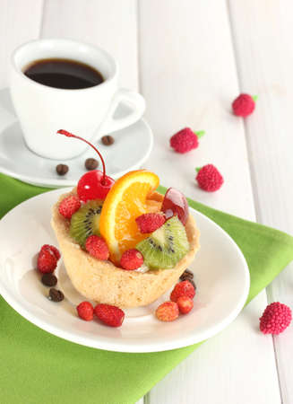 sweet cake with fruits on plate and cup of coffee on wooden table photo