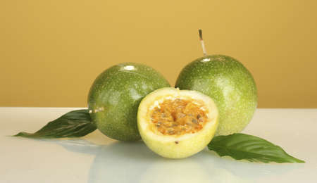 green passion fruit on yellow background close-up photo