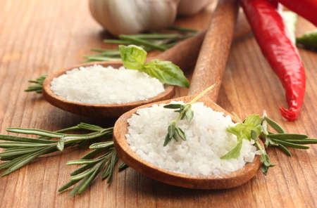 salt in spoons with herbs and vegetables isolated on white photo