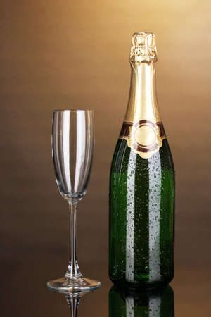 gold capped: Bottle of champagne and goblet on brown background Stock Photo