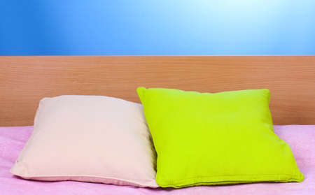 bright pillows on bed on blue background photo