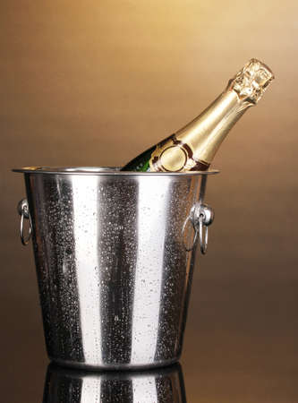 Bottle of champagne in bucket on brown background photo