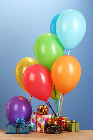 colorful balloons holding a gifts on a wooden table on blue background photo