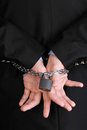 fettered: Businessman hands fettered with chain and padlock