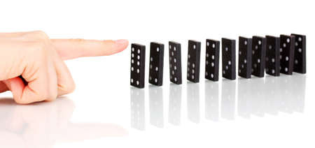 Hand pushing dominoes isolated on white photo