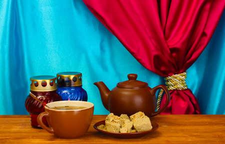 confect: Teiera con tazza e piattino con dolci halva su tavola di legno su uno sfondo di tenda close-up Archivio Fotografico