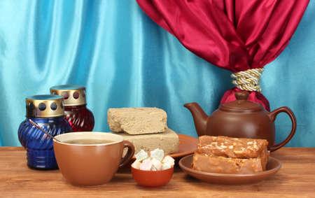 confect: Teiera con tazza e piattino con dolci orientali - sorbetto, halva e Turkish Delight su tavola di legno su uno sfondo di tenda close-up Archivio Fotografico