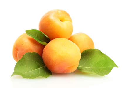 the peach: ripe sweet apricots with green leaves isolated on white Stock Photo