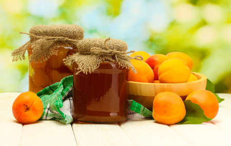 canned apricots and jam in a jars and ripe apricots in bowl on wooden table on green background photo