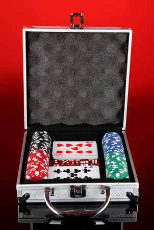 Poker set in metallic case on bright red background photo