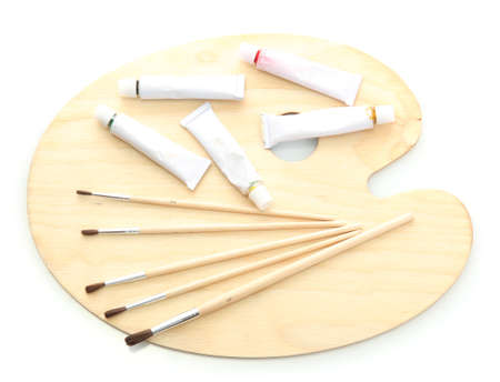 wooden art palette, tubes with paint and brushes isolated on white photo