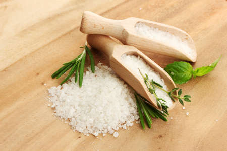 salt in shovels with fresh basil, rosemary and thyme on wooden background photo