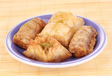 Sweet baklava on plate on bamboo mat photo