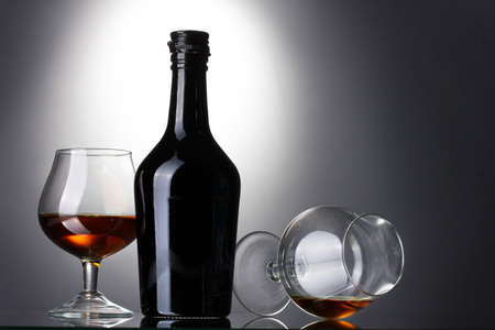 distilled alcohol: Glasses of brandy and bottle on gray background
