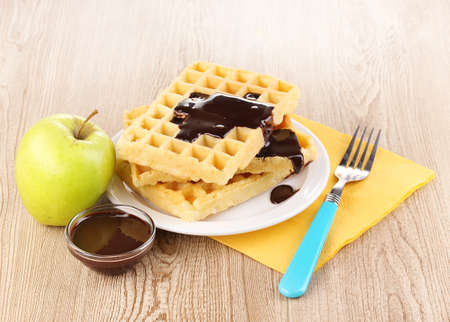 Tasty waffles with chocolate on plate on wooden background photo