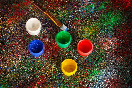spattered: Frascos con guache colorido y pincel sobre fondo negro, salpicado con pintura de colores close-up Foto de archivo