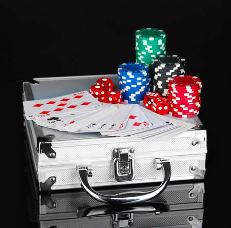 Poker set on a metallic case isolated on black background photo
