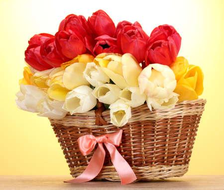flores de cumpleaños: bellos tulipanes en la cesta sobre la mesa de madera sobre fondo amarillo Foto de archivo