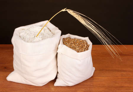 gunny bag: Flour and wheat grain on wooden table on dark background