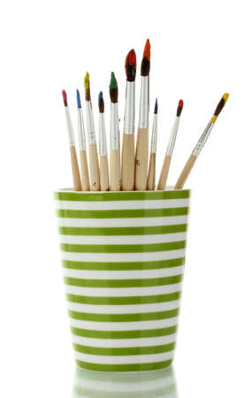 gouache: Paint brushes with gouache in cup isolated on white