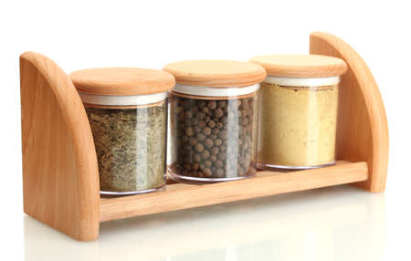 jars with spices on wooden shelf isolated on white photo