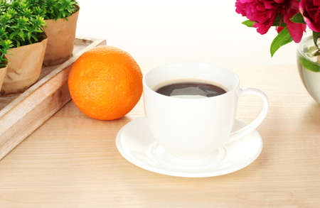 cup of coffee, orange and flowers on table in cafe photo
