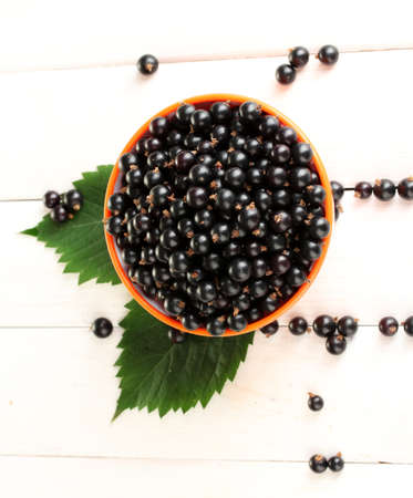 Fresh black currant in colorful bowl on white wooden background close-up photo