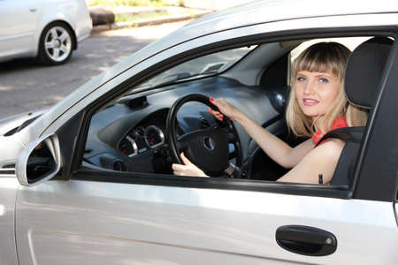 Happy smiling blonde woman in car photo