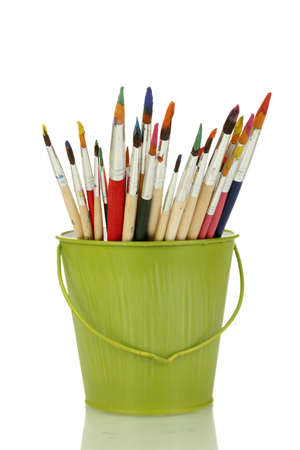 Paint brushes with gouache in bucket isolated on white photo