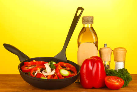 panful: frying pan with vegetables on yellow background Stock Photo