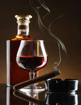 whisky: bottle and glass of brandy and cigar on brown background