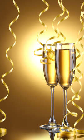 champagne glasses: glasses of champagne and streamer on yellow background