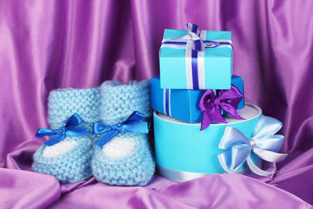 blue baby boots and gifts on silk background  photo