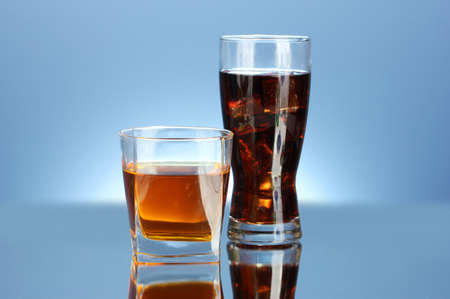 glass of whiskey and a glass of cola on blue background close-up photo
