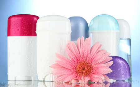 deodorant botttles with flower on blue background photo