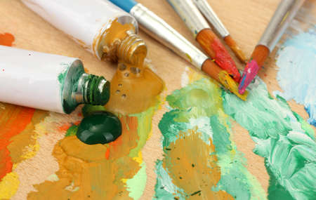 Abstract acrylic paint, paint tubes and brushes on wooden  palette Stock Photo - 14536724
