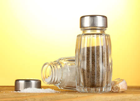 Salt and pepper mills, on wooden table on yellow background photo