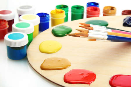wooden art palette with  paint and brushes isolated on white Stock Photo - 14536546