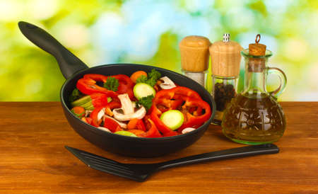panful: frying pan with vegetables on green background Stock Photo