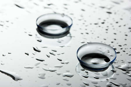 shortsightedness: contact lens with drops on grey background