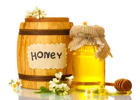 Zoete honing in vat en kruik met acacia bloemen op wit wordt geïsoleerd