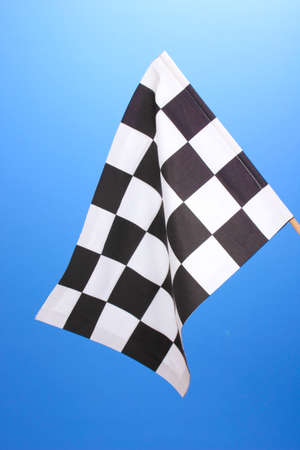 Checkered finish flag on blue background photo