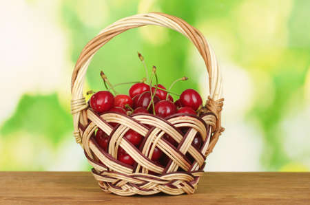 cherry in basket on wooden table on green background photo
