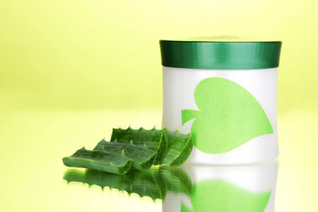 Jar of cream with aloe vera on green background photo